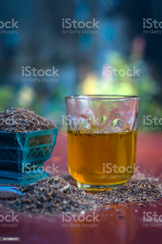 Black cumin seeds,shah jerra,Nigella sativa  and its extracted water in a transparent glass on brown wooden surface.; stock photo