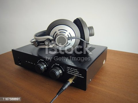Black DAC Headphone amplifier with connected headphones on the wooden desk
