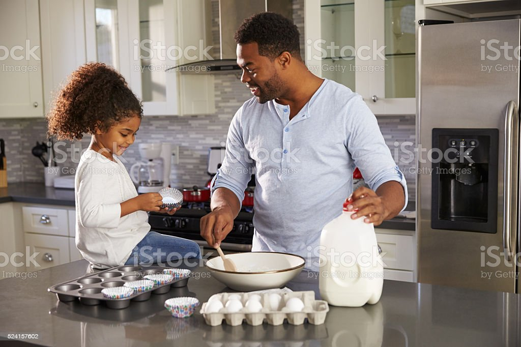 Black dad and young daughter baking together in the kitchen stock photo