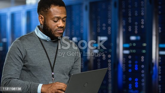 1131208605 istock photo Black Data Center IT Technician Standing in Server Rack Corridor with a Laptop Computer. He is Visually Inspecting Working Server Cabinets. 1131198138