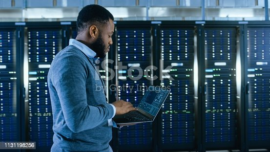 1131208605 istock photo Black Data Center IT Technician Walking Through Server Rack Corridor with a Laptop Computer. He is Visually Inspecting Working Server Cabinets. 1131198256