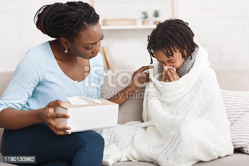 Seasonal Infectious Disease, Epidemic. African girl sneezing, having runny nose. Black mom with napkins