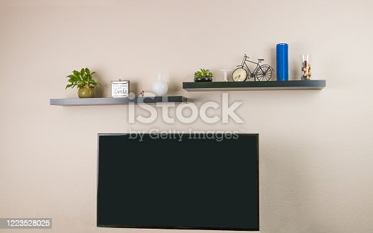 Black wall mounted and decorated shelves and wall mounted television unit are mounted and displayed on the wall.