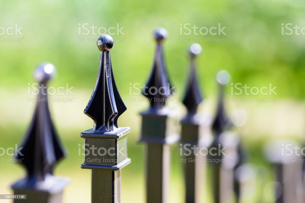 Black decorative metal fence, angular iron rods and curved upper part. Close-up of the top ornaments. stock photo