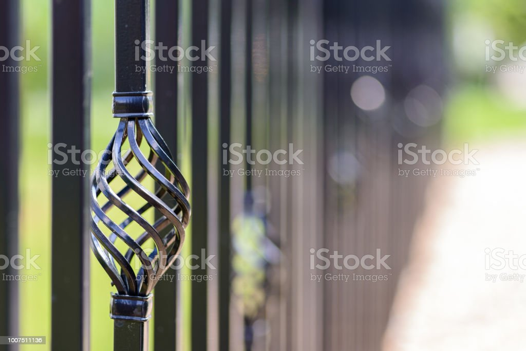 Black decorative metal fence, angular iron rods and curved upper part. Close-up of the decoration on the side. stock photo