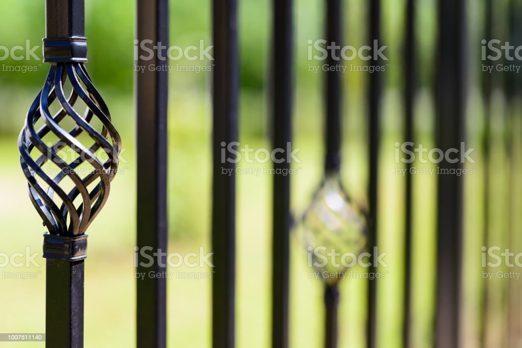 Black decorative metal fence, angular iron rods and curved upper part. Close-up of the decoration, front view. stock photo