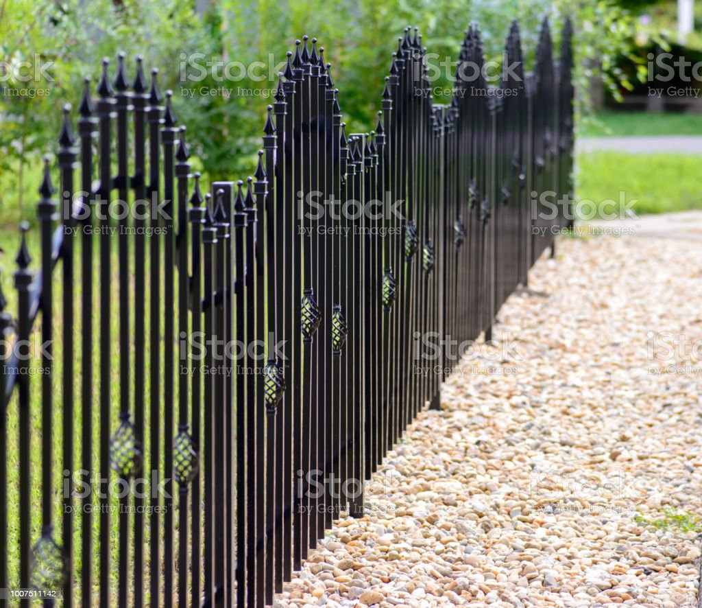Black decorative metal fence, angular iron rods and curved upper part. stock photo