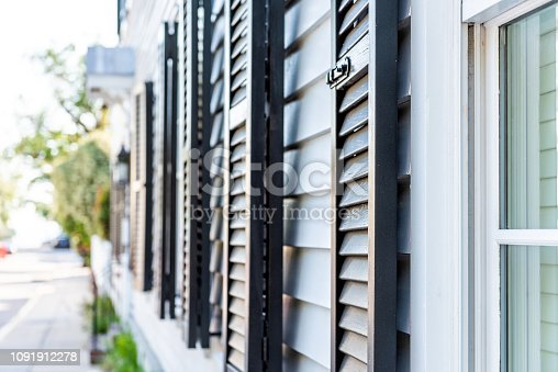Black decorative row of window shutters closeup architecture open exterior of houses buildings or homes in Charleston, South Carolina southern city