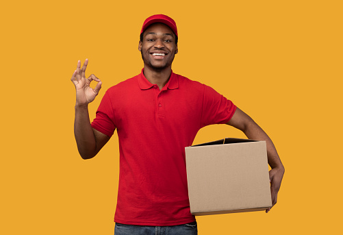 Fast Shipment Concept. Portrait of positive african american delivery guy wearing red cap and uniform holding cardboard box and showing okay sign gesture standing isolated over orange studio wall