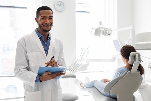 istock Black dentist smiling and holding folder in dental cabinet 1222938825