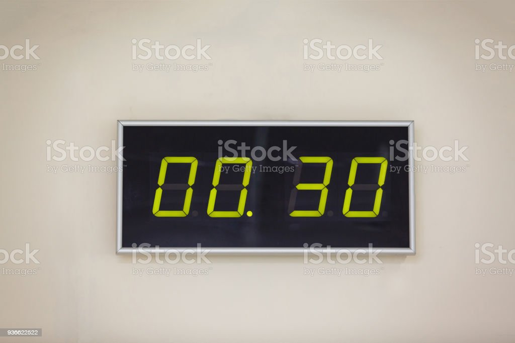 Black digital clock on a white background showing time 0 hours 30 minutes stock photo