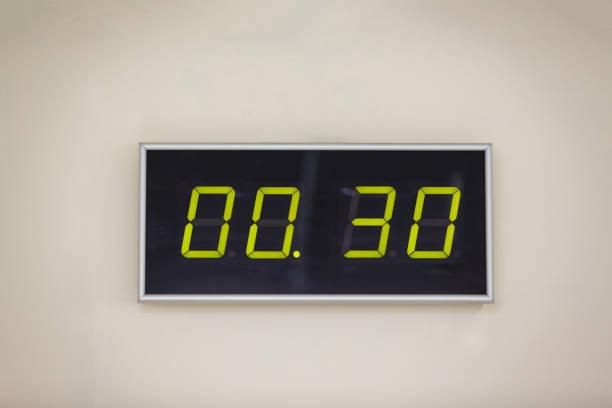 schwarz digitaluhr auf weißem hintergrund zeigt zeit 0 stunden 30 minuten - led uhr stock-fotos und bilder