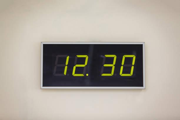 schwarz digitaluhr auf weißem hintergrund zeigt mal 12 stunden 30 minuten - led uhr stock-fotos und bilder