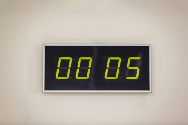 black digital clock on a white background showing time hours minutes - timer stock photos and pictures