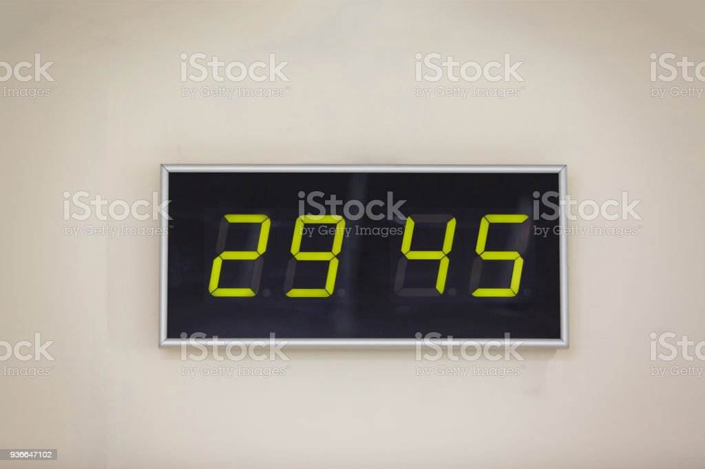 Black digital clock on a white background showing time hours minutes stock photo