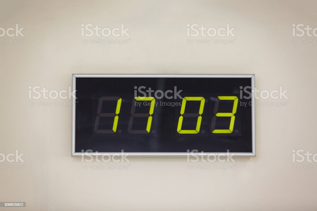 Black digital clock on a white background showing time Patrick's stock photo