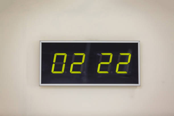 Black digital clock on a white background showing time stock photo