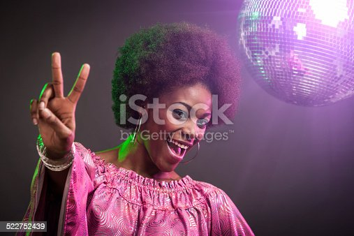 An attractive young african american woman dressed in pink retro styled 1970's attire dancing in a disco nightclub.