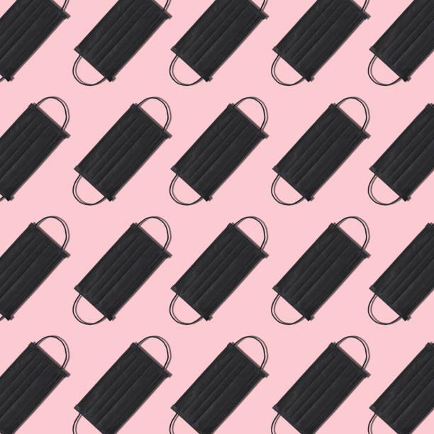 Black disposable medical face mask pattern on pink background