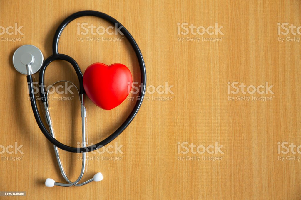 Black doctor stethoscope and stress ball in heart shape on wooden...