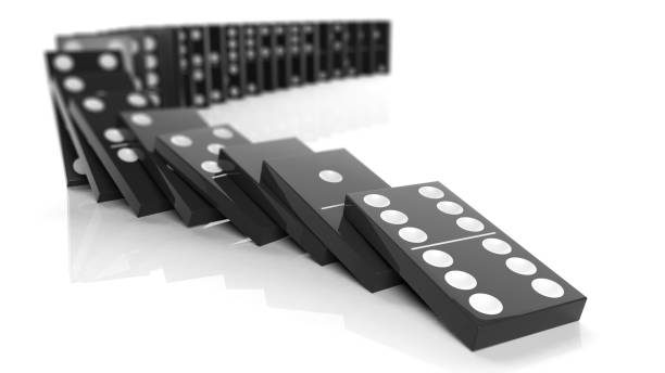 Black domino tiles falling in a row, isolated on white stock photo