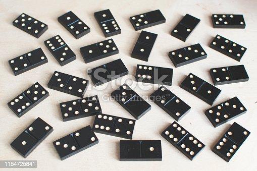 black dominoes on light wooden background