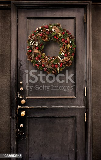 Full frame of a mysterious old wooden black door hanging a Christmas Wreath.