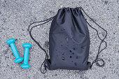 黒巾着リュック、地面、トップ ビューにダンベルとフィットネス スポーツ バッグ