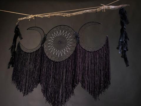 black dreamcatcher in front of a dark background