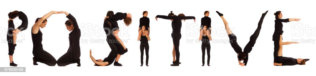 Black dressed people forming word POSITIVE royalty-free stock photo