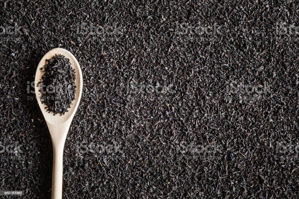 Black, dried, loose tea with wooden spoon. Enjoying of tea break at the work, at home, at visit with friends, family or alone everyday. Empty place for text how to prepare a drink. Top view. stock photo