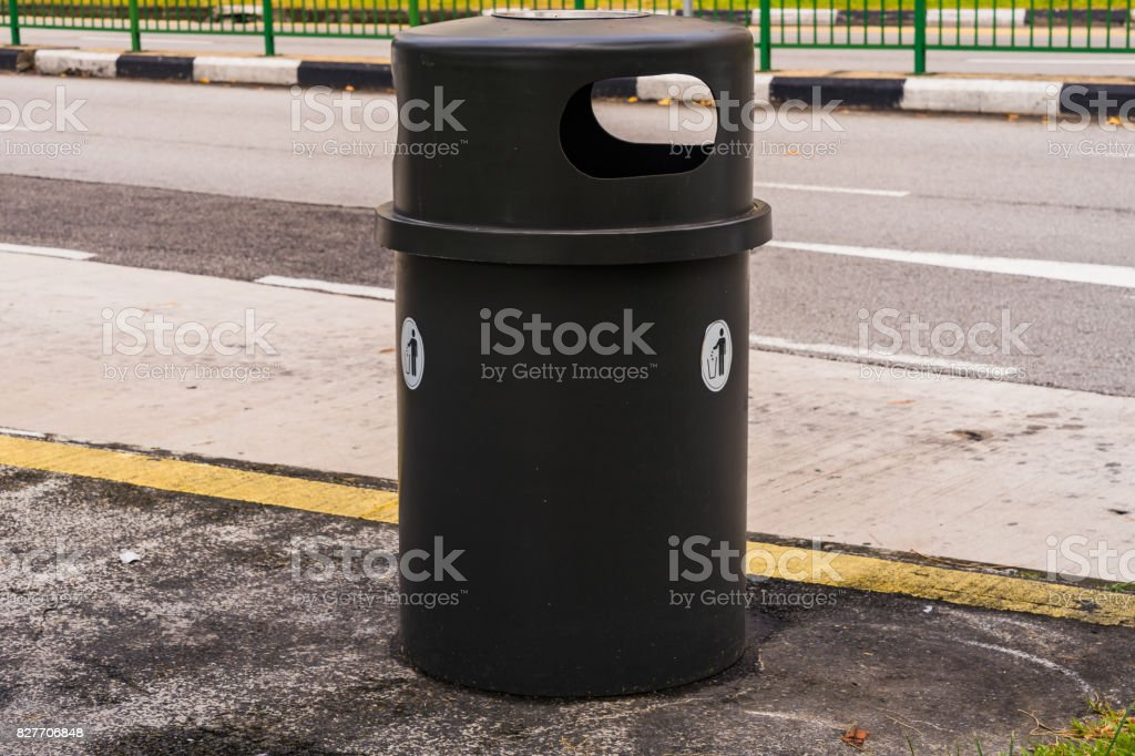 Black dustbin or trashcan beside the road stock photo