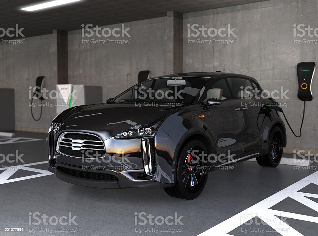 Black electric SUV recharging in parking garage stock photo