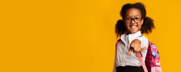 Black Elementary School Girl Pointing Finger At Camera, Panorama Hey, you. Happy Black Elementary School Girl Pointing Finger At Camera On Yellow Studio Background. Panorama With Copy Space nerd hairstyles for girls stock pictures, royalty-free photos & images
