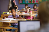 istock Black elementary schoolgirl listening to her teacher on a class in the classroom. 1157339572