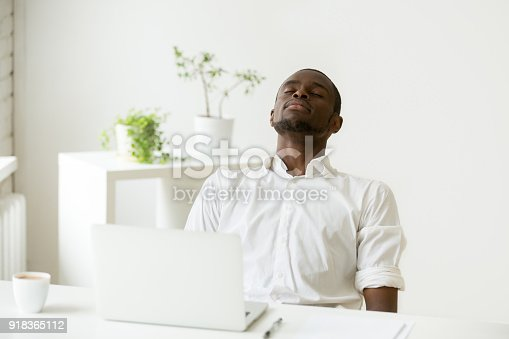 istock Black employee taking rest doing exercise for relaxation at workplace 918365112