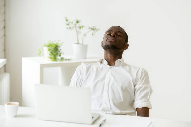 Black employee taking rest doing exercise for relaxation at workplace stock photo