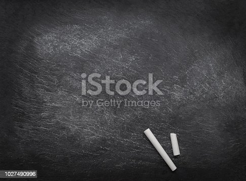 istock Black empty chalk board with two pieces of chalk. Copyspace. Back to school concept. 1027490996