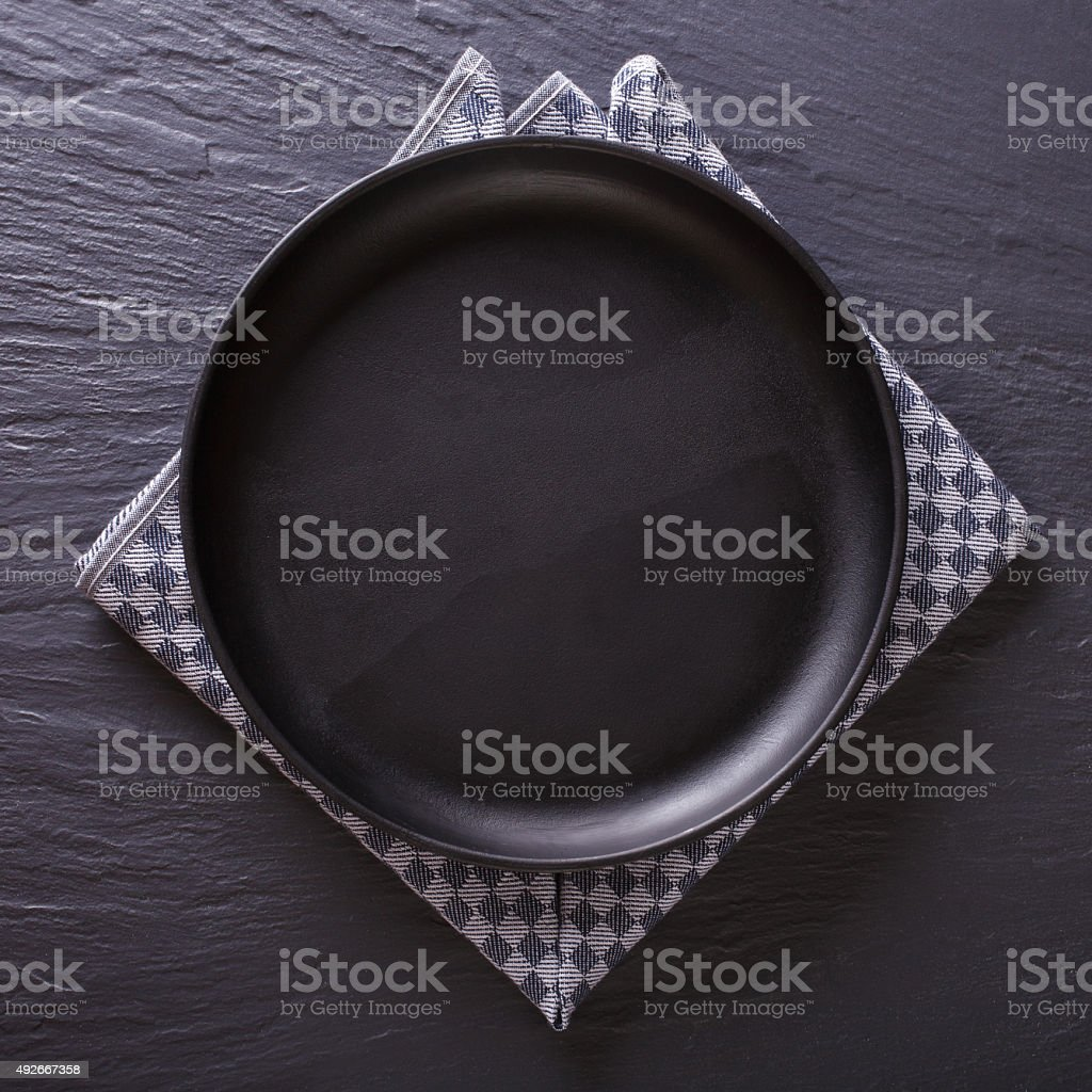 Black empty plate on the table. top view stock photo
