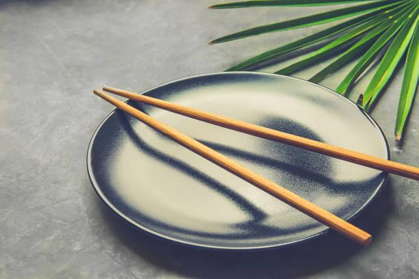 Assiette vide noir avec feuille d'arbre de palmier bambou brun baguettes sur fond de Pierre béton gris foncé. Concept de Cuisine chinoise Thai asiatique. Modèle de menu affiche recette. Espace copie tonifié - Photo