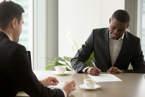 843533912 istock photo Black entrepreneur singing contract at office 843533912