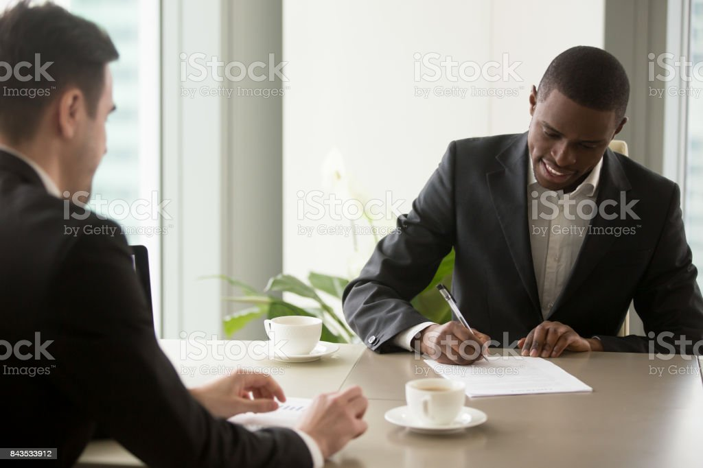 Black entrepreneur singing contract at office stock photo