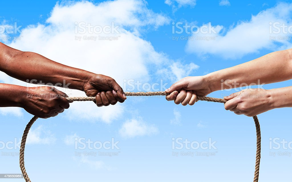 black ethnicity arms with hands pulling rope against white Caucasian...