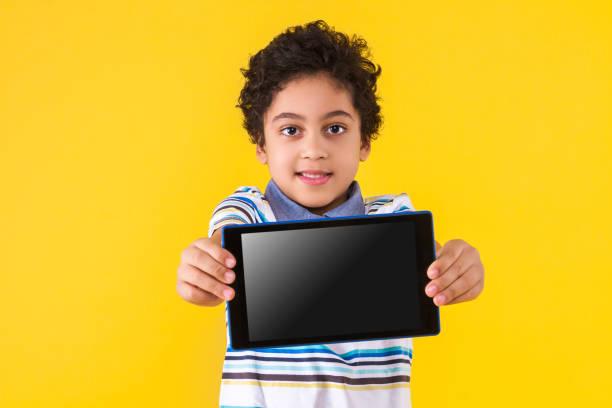 Black ethnicity child boy isolated on yellow background stock photo