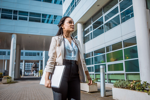 A black ethnicity female professional business woman outdoors on an office complex in the Spring daytime