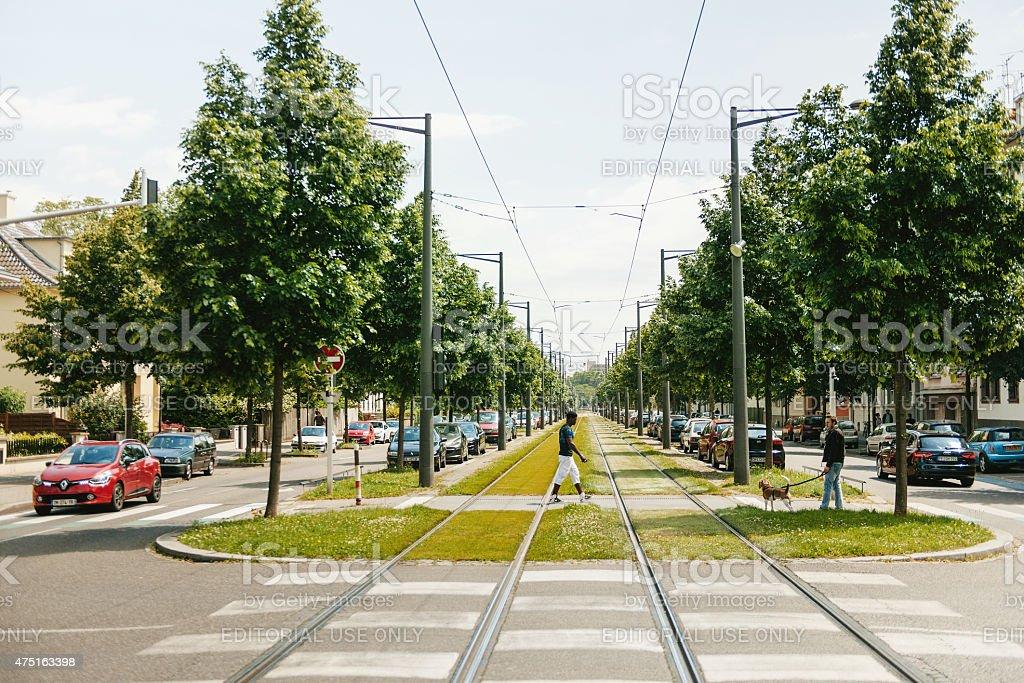 Black ethnicity man crossing tram railway stock photo