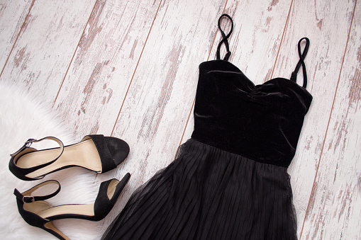 istock Black evening dress and shoes on a wooden background. Fashion concept. Top view, space for text 644521848