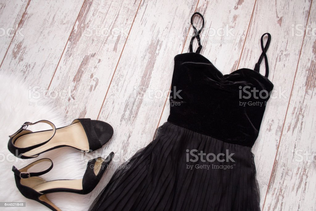 Black evening dress and shoes on a wooden background. Fashion concept. Top view, space for text stock photo
