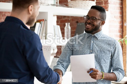 Mixed race executive company ceo shaking hands with client during business negotiations meeting in office. African american recruiter greeting handshaking with vacancy candidate before job interview