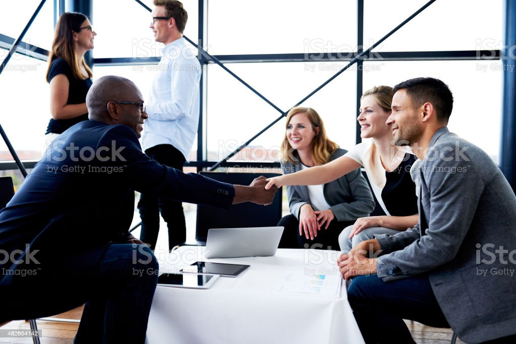 Black executive shaking hands with female colleague stock photo